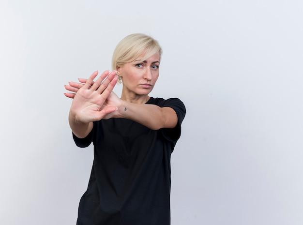 Poważna blondynka słowiańska blondynka w średnim wieku patrząc na kamery robi gest stop na białym tle na białym tle z miejsca na kopię