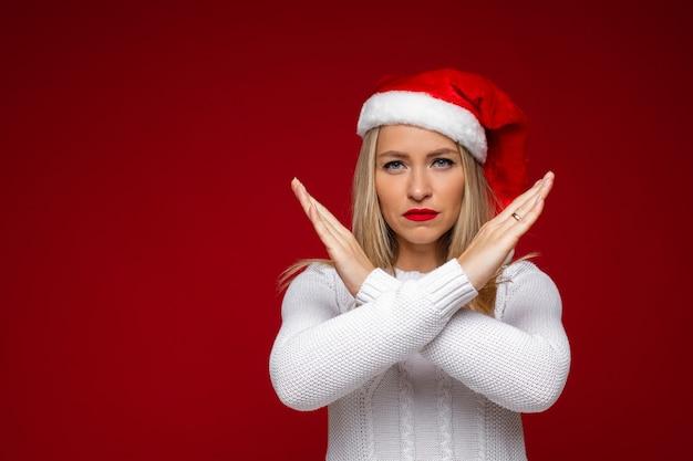 Poważna blondynka w santa hat i białym swetrze pokazano skrzyżowane ramiona. pojęcie zakazu.