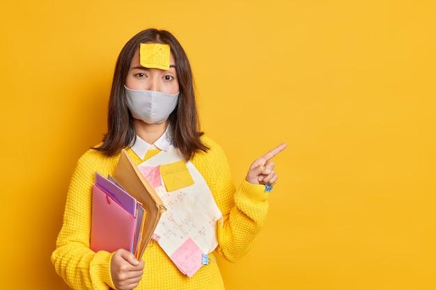 Poważna brunetka azjatka ma naklejkę na głowie próbuje uczyć się informacji, aby pomyślnie zdać egzamin, nosi jednorazową maskę, aby zapobiec punktom koronawirusa w pustej pustej przestrzeni
