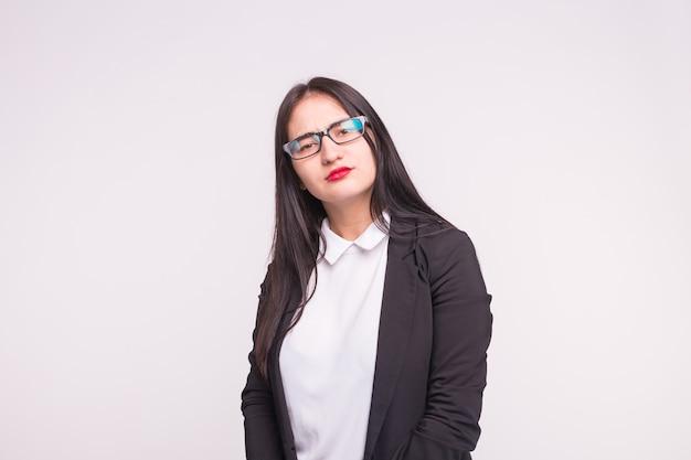 Poważna brunetka dziewczyna w studio w okularach na białym tle