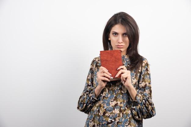 Poważna brunetka kobieta pokazuje książkę.