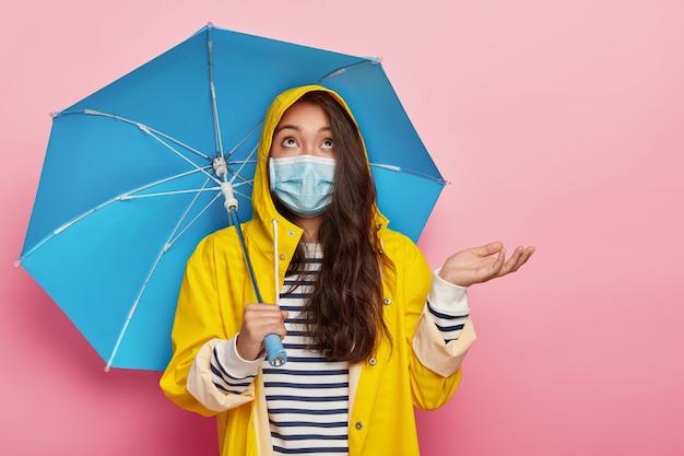 Poważna brunetka unosi dłoń, nosi maseczkę medyczną, chroniącą się przed wirusami i chorobami