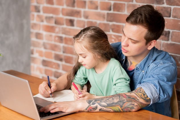 Poważna, ciekawa córeczka siedzi na kolanach ojca przy stole i sprawdza notatki ojca w dzienniku, pomagając mu w pracy w domu