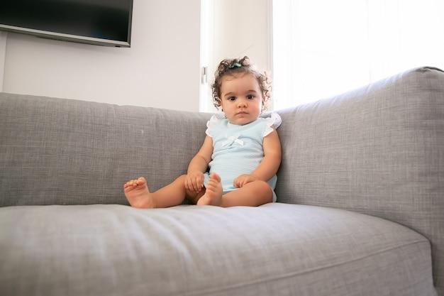 Poważna ciemnowłosa dziewczynka ubrana w jasnoniebieski materiał, siedząca na szarej kanapie w domu, a. dziecko w domu i koncepcji dzieciństwa