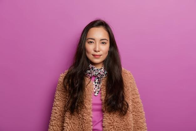 Poważna ciemnowłosa kobieta w brązowym płaszczu, ma zdrową skórę, minimalistyczny makijaż, wygląda z czarującym wyrazem
