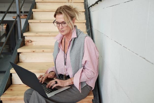 Poważna dojrzała bizneswoman skupiona na sprawach zawodowych siedząca na schodach i przeglądająca pliki na laptopie