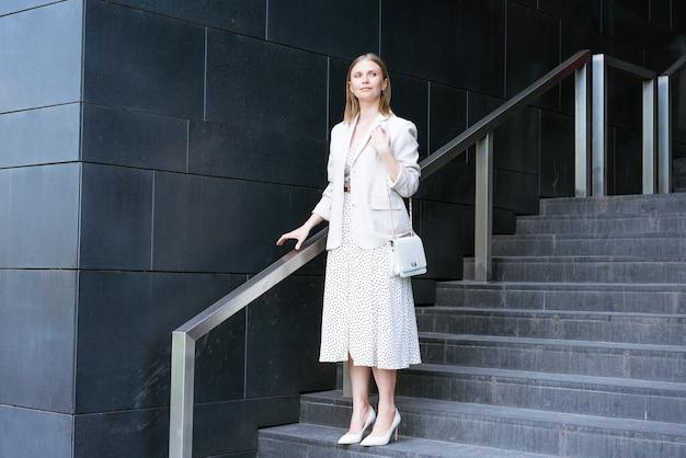 Poważna dojrzała bizneswoman w eleganckiej sukience stojąca na schodach przed biurem...