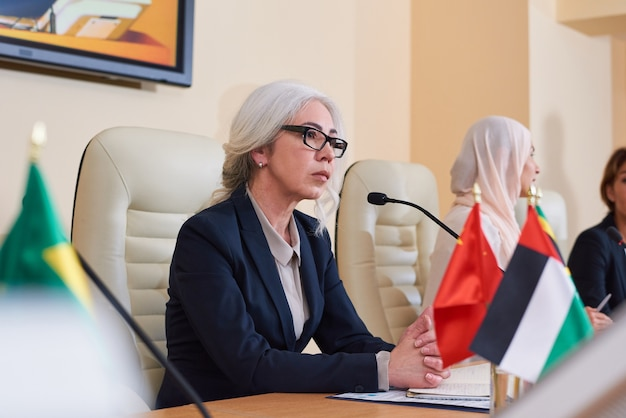 Poważna, dojrzała delegatka w eleganckim garniturze słucha pytań publiczności przed udzieleniem im odpowiedzi na konferencji
