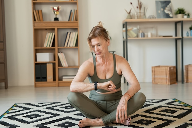 Poważna dojrzała sportsmenka patrząc na smartwatcha siedząc na podłodze w salonie i przerywając po treningu w domu