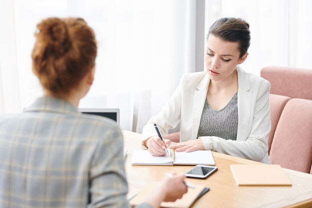 Poważna doświadczona pani rekrutująca siedząca przy stole i robiąca notatki podczas rozmowy kwalifikacyjnej z kandydatem do pracy w kawiarni