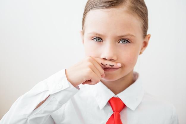 Poważna dziewczynka z malowanymi wąsami. koncepcja feminizmu