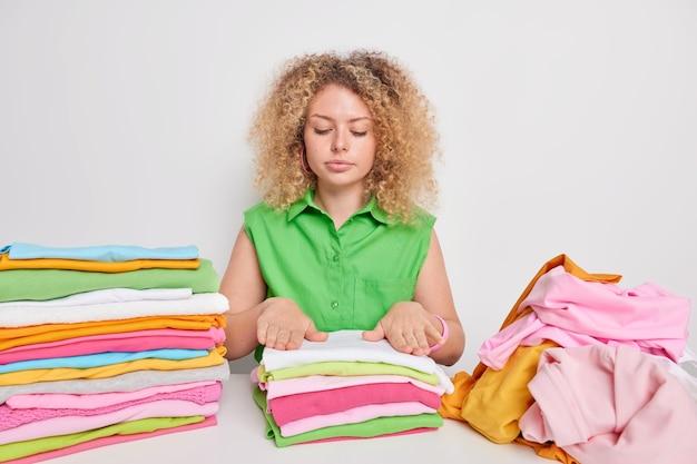 Poważna gospodyni domowa z kręconymi włosami składa pranie ładnie przynosi ubrania w porządku siada przy stole