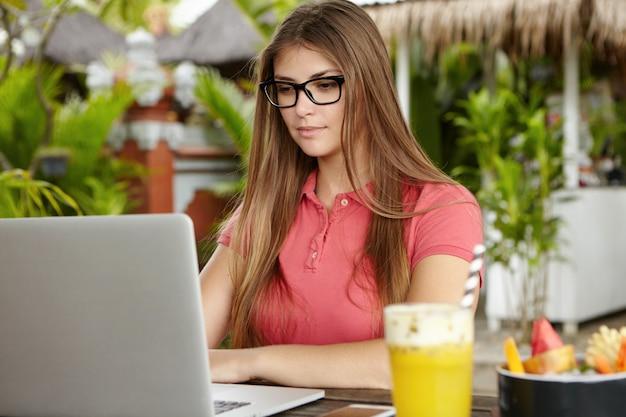 Poważna i pewna siebie freelancerka w prostokątnych okularach za pomocą laptopa do pracy zdalnej podczas wakacji, siedząca w letniej kawiarni podczas śniadania, popijająca zdrowy koktajl owocowy.