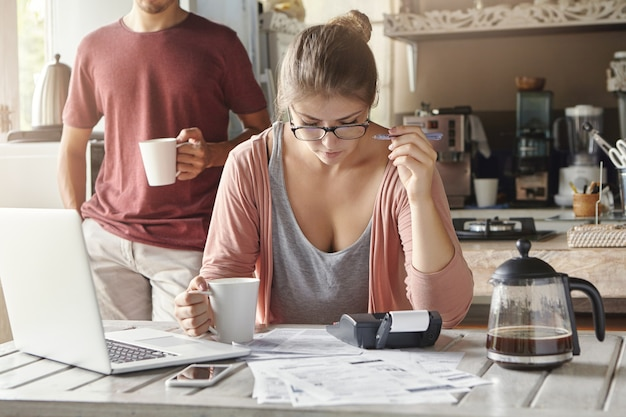Poważna i skoncentrowana młoda kobieta w okularach trzymająca kubek w jednej ręce i długopis w drugiej, skupiona na papierkowej roboty