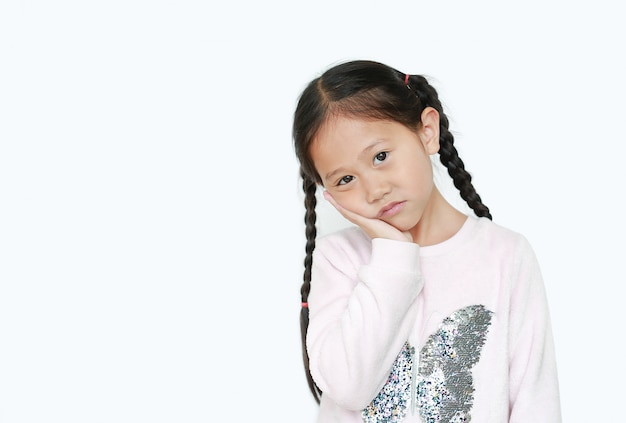 Poważna i smutna azjatycka mała dziewczynka z posturą jej rękę na policzku