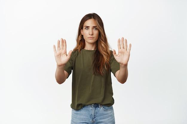 Poważna i surowa dorosła kobieta, matka wykazująca tabu, gest zakazu, zabronić, odmówić lub powstrzymywać kogoś od robienia złych rzeczy