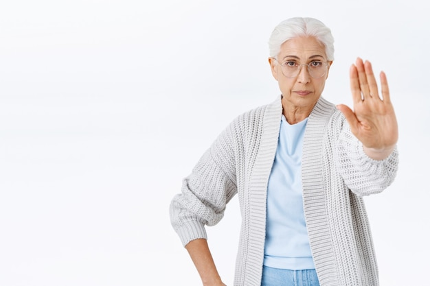 Poważna i surowa staruszka, babcia zabrania, wyciągnij rękę do przodu w geście zatrzymania, odrzucenia lub zakazu, wygląda na zdeterminowaną i pewną siebie, nie pozwól synowi palić, stoi biała ściana