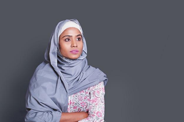 Poważna indyjska muzułmańska młoda kobieta stojąca na szarym tle
