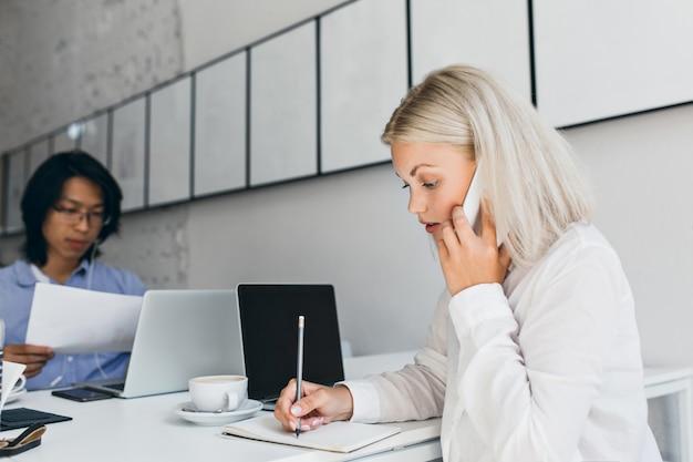 Poważna jasnowłosa kobieta rozmawia przez telefon i pisze coś na papierze