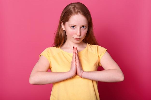 Poważna kaukaska kobieta pozuje z pewną siebie ekspresją, trzyma ręce w geście modlitwy, ubrana w żółtą koszulkę, na różowo.