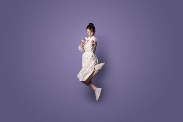 Poważna kaukaska kobieta skacząca na fioletowej ścianie z wolną przestrzenią i wskazująca bezpośrednio