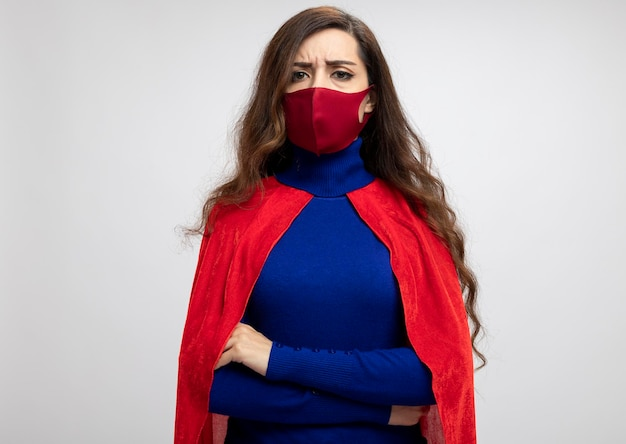 Poważna kaukaski dziewczyna superbohatera z czerwoną peleryną na sobie czerwoną maskę ochronną