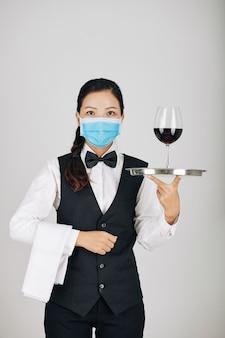 Poważna kelnerka niosąca wino