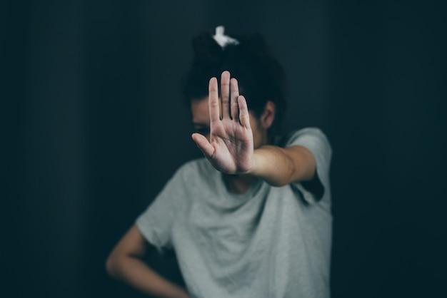 Poważna kobieta gestem zatrzymania odizolowana na czarnym tle