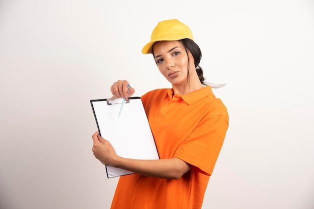 Poważna kobieta kurier pokazując schowek na białej ścianie.