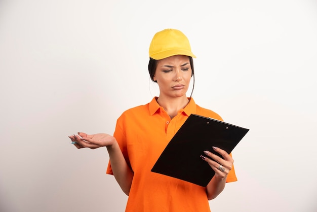 Poważna kobieta kurier z ołówkiem patrząc na schowek na białej ścianie.
