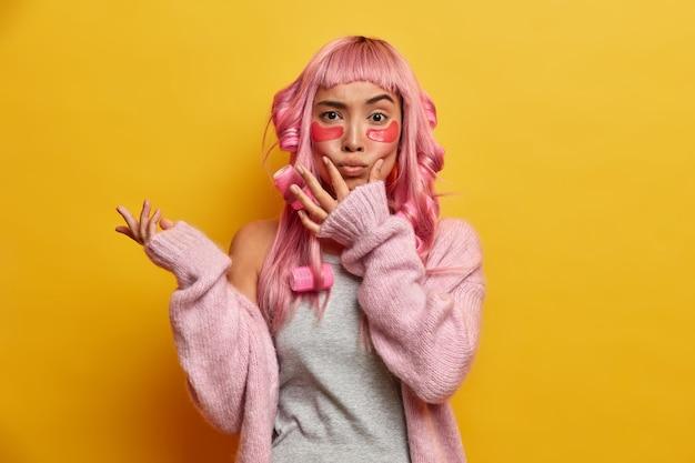 Poważna kobieta ma zaróżowione włosy, trzyma dłonie na twarzy i robi grymas, wydyma usta, układa lokówki, nosi kolagenowe łaty odmładzające skórę