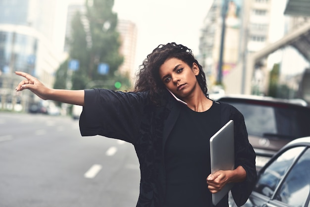 Poważna kobieta rasy mieszanej używa telefonu, spróbuj wziąć taksówkę. filtrowany obraz