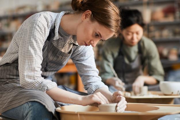 Poważna kobieta robi garnkowi w warsztacie