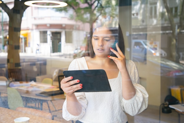 Poważna kobieta rozmawia na komórce, używając tabletu i patrząc na ekran