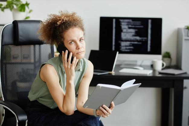 Poważna kobieta rozmawia przez telefon komórkowy i planuje swój dzień, siedząc na krześle z notatnikiem w biurze