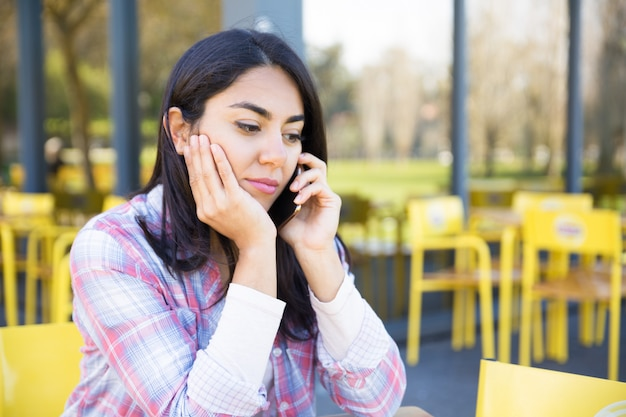Poważna kobieta rozmawia przez telefon komórkowy w kawiarni na świeżym powietrzu