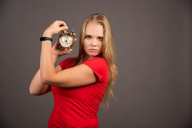 Poważna kobieta stojąca na czarnej ścianie z zegarem.