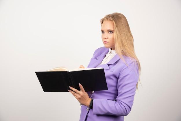 Poważna kobieta trzyma otwarty tablet na biały.