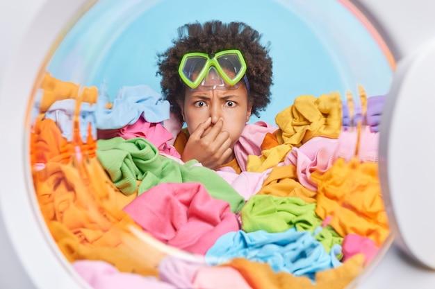 Poważna kobieta udaje, że nurkuje w pralce, wstrzymuje oddech, trzyma rękę na nosie, nosi maskę do nurkowania, utonęła w stercie wielokolorowego prania, wykonuje prace domowe