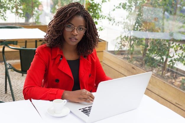 Poważna kobieta używa laptop i patrzejący