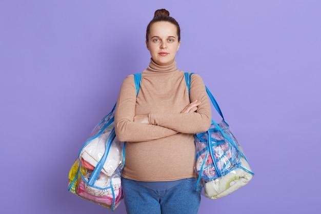 Poważna kobieta w ciąży z rękami skrzyżowanymi na piersi