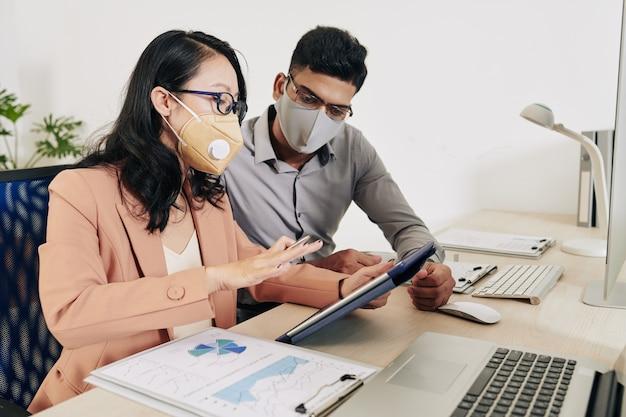 Poważna kobieta w masce ochronnej i okularach pokazująca koledze prezentację swojego pomysłu na tablecie