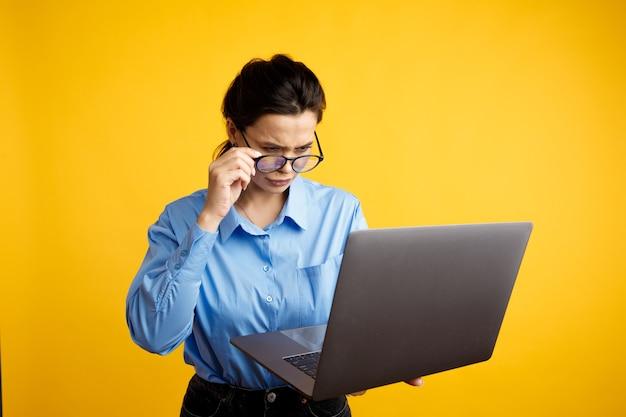Poważna kobieta w okularach trzymając laptopa i używając go na białym tle na żółtym tle.