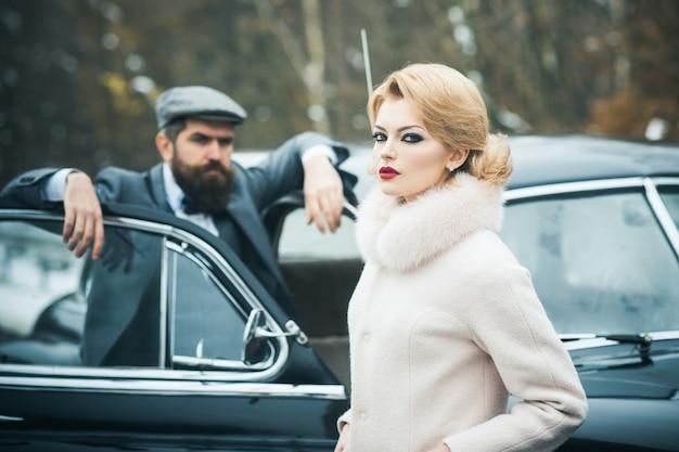 Poważna kobieta w płaszczu i brodaty kierowca mężczyzna retro para w pobliżu rocznika samochodu