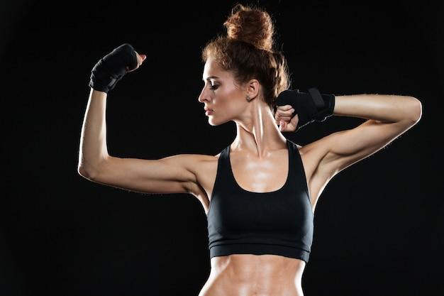 Poważna kobieta wojownik pokazano jej biceps