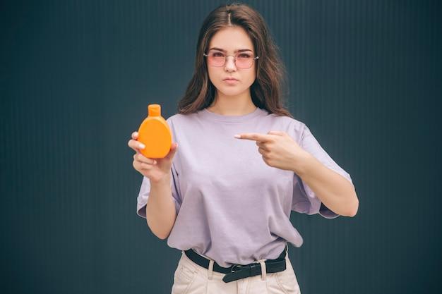 Poważna kobieta wskazująca na pomarańczową butelkę z kremem ochronnym do opalania w butelce z spf