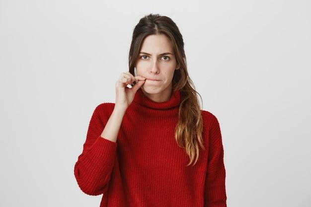 Poważna kobieta zapinająca usta, zachowaj tajemnicę