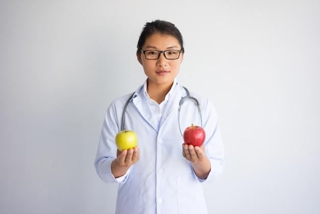Poważna ładna azjatycka kobiety lekarka z czerwonym i żółtym jabłkiem.
