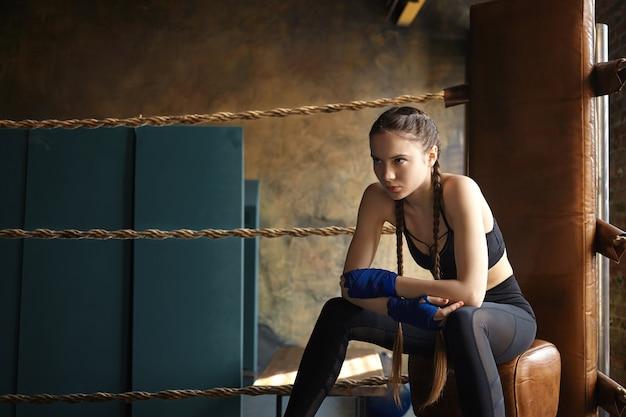 Poważna ładna dziewczyna z dwoma warkoczami, nastawiona na walkę, siedząca na ringu bokserskim, wpatrująca się przed siebie z skupionym spojrzeniem. sztuki walki