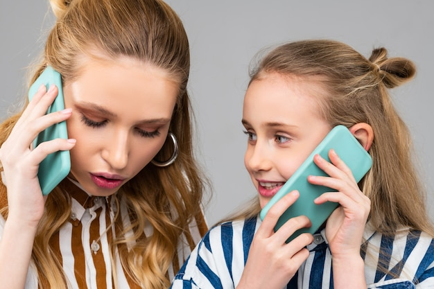 Poważna ładna kobieta ma ważny telefon podczas pobytu z siostrą, gdy nosi smartfon